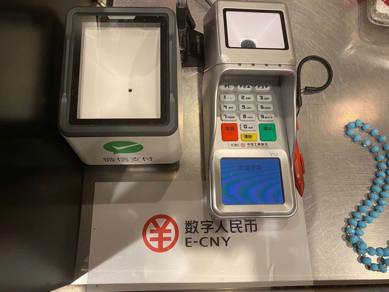 一家商户收银台上的数字人民币可使用提示以及刷码设备 图 记者 叶映荷